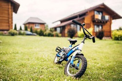 Children bike on a green lawn in the courtyard of a country house - rural property