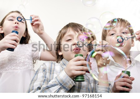 children blowing soap bubbles together