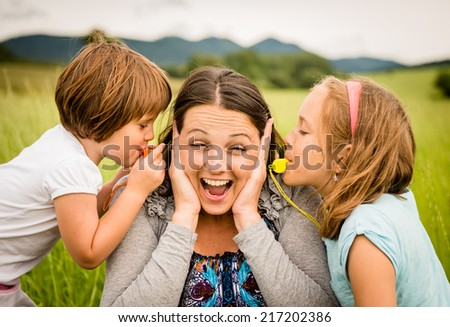 Children blowing whistles to mother\'s ears- outdoor in nature