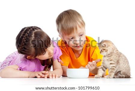 children boy and girl feeding kitten