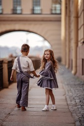 Children boy and girl in retro clothes are walking down the street holding hands. The little girl turned around. Romantic, historical image. Selective focus