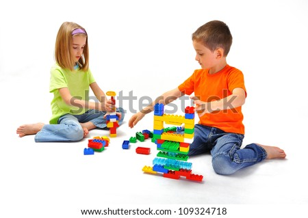 Children, boy and girl playing with constructor sitting on the floor, isolated on white