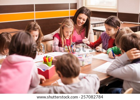 Children boys and girls sitting together around the table in classroom and drawing. With them is their young and beautiful teacher.