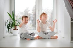 Children boys in pajamas on the windowsill, zen and meditation, calm