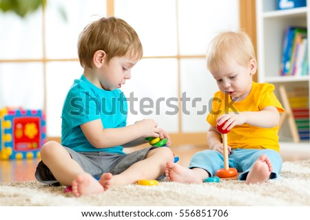 Children boys play with educational toys in preschool or kindergarten. Toddler kid and baby build pyramid toys at home or daycare. #556851706