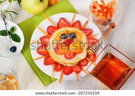 Children breakfast pancakes smiling face of the sun lion strawberry blueberry and apricot, cute food, honey, creative idea for kids dinner lunch food pictures