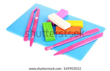 Children bright plasticine on desk with stacks isolated on white - stock photo