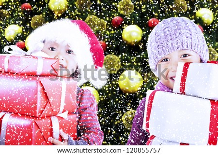 Children bring christmas gifts under the tree while snowing