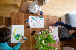 Children, brothers, drawing with aquarel paints at home, shot from above
