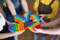 children brought to kindergarten a popular toy pop it, hold in their hands anti-stress, silicone game