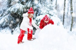 Children build snowman. Kids building snow man playing outdoors on sunny snowy winter day. Outdoor family fun on Christmas vacation. Boy and girl play snow balls. Winter clothing for baby and toddler