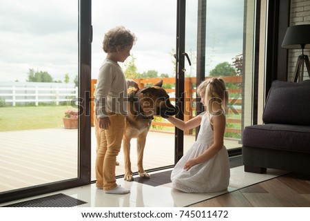 Stock Photo Children caressing watch dog protecting home, kids playing with big pet coming inside house, little boy and girl having fun stroking german shepherd standing at door, leisure with domestic animal