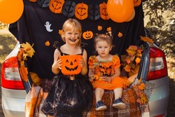 Children celebrating Halloween in trunk of car.