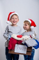 Children charity. school boy and girl in Santa Clause hats. Charity with donate box. Delivery and donation concept. Happy Xmas and New Year holiday! Christmas gifts.