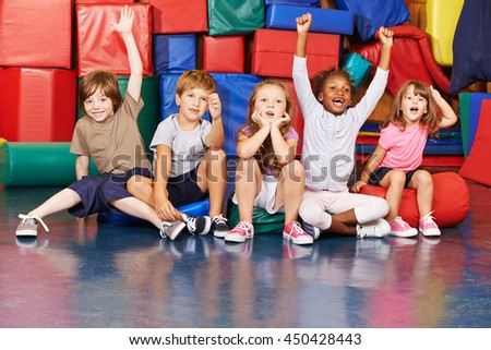 Children cheering together after victory in gym of a pre school