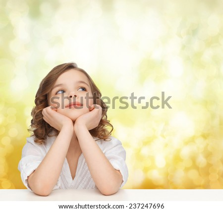 children, childhood, holidays and happy people concept - beautiful girl sitting at table, looking up and dreaming over yellow lights background