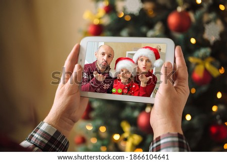 Children congratulate their parents via video conference. A woman holds a digital tablet in her arms and see how they blow a kiss a greeting on Christmas eve.