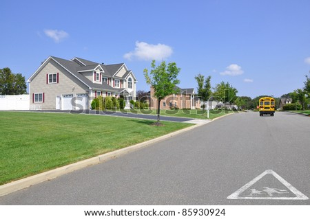 Children Crossing School Traffic Symbol on Residential Suburban Street School Bus Stop Sign Extended down the block Sunny Blue Sky Day