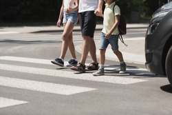 Children crossing the street with their father