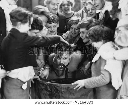 Children crowded around apple bobbing