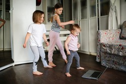 Children dance at home in the living room, funny children have fun at home.
