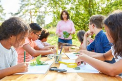 Children do handicrafts and draw plants in creative art class at summer camp