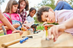 Children do handicrafts and work with wood in the workshop at the holiday camp