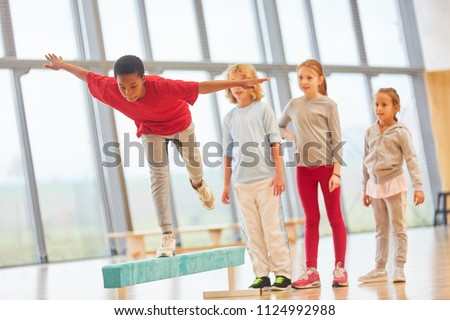 Children do school sports and balance on a balance beam