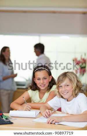 Children doing their homework with their parents behind them