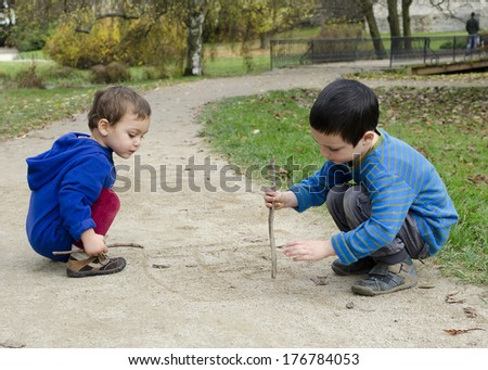 Children drawing into sand on a path in park