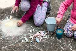 Children drawing with chalk on the concrete sitting on the ground. Art therapy, CBT, simple creativity excercises. Two girls drawing with colorful chalk. Outdoor activities, lifestyle