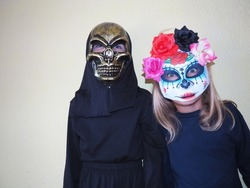 Children dressed in black costumes and scary Halloween masks. Girl in a Mexican Kalaka Calavera mask. A boy wearing a horrible skull mask with a black hood. All Hallows Eve or All Saints Eve theme.