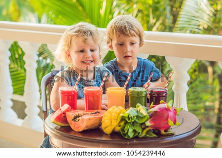 Stock Photo Children drink colorful healthy smoothies.. Watermelon, papaya, mango, spinach and dragon fruit. Smoothies, juices, beverages, drinks variety with fresh fruits on a wooden table