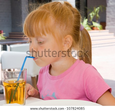 Children drinking fruit juice in cafe