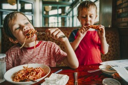 children eat unhealthy food in a cafe. kids enjoy pasta and pizza