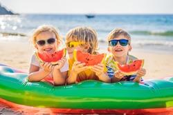 Children eat watermelon on the beach in sunglasses