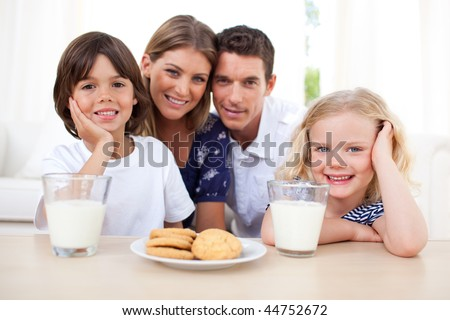 Children eating biscuits and drinking milk with their parents in the kitchen