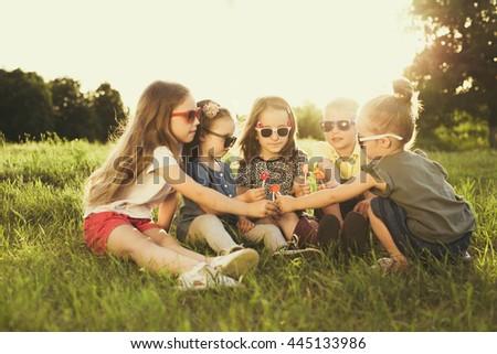 Children eating lollipops during summertime fun #445133986