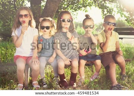Children eating lollipops during summertime fun #459481534