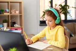 children, education and distant learning concept - student girl in headphones doing school test at home