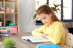 children, education and learning concept - little student girl reading book at home
