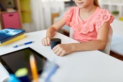 children, education and technology concept - close up of student girl using smart speaker at home