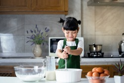 children enjoy cooking in the kitchen. Happy Asian kid is preparing the dough, bake cookies in the kitchen.