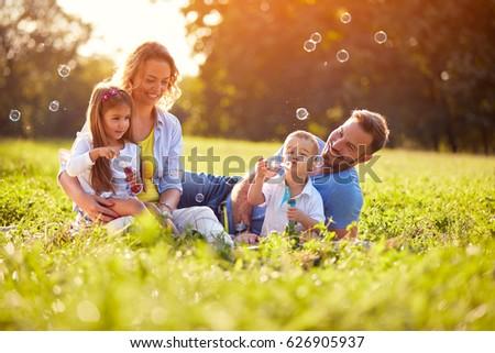Children enjoying in making soap bubbles outside  - Shutterstock ID 626905937