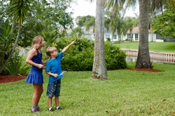 Children explore nature in their neighborhood, collecting items for a scavenger hunt and pointing at a bird nest