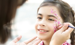 Children face painting. Little girl having fun, making creative floral design outdoors, copy space