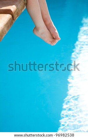 Children feet against blue swimming pool. Summer vacations concept