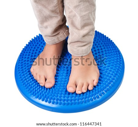 Children feet on the massage pillow, isolated on white background