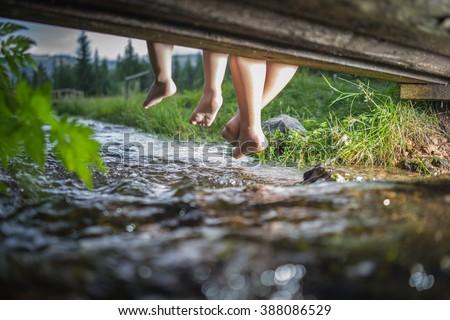 Children feet playing and having fun time on the beautiful mountain creek