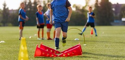 Children football player with training hurdles. Soccer agility training equipment. Kids playing sports on grass field. Happy boys practice sports. Kids football speed training